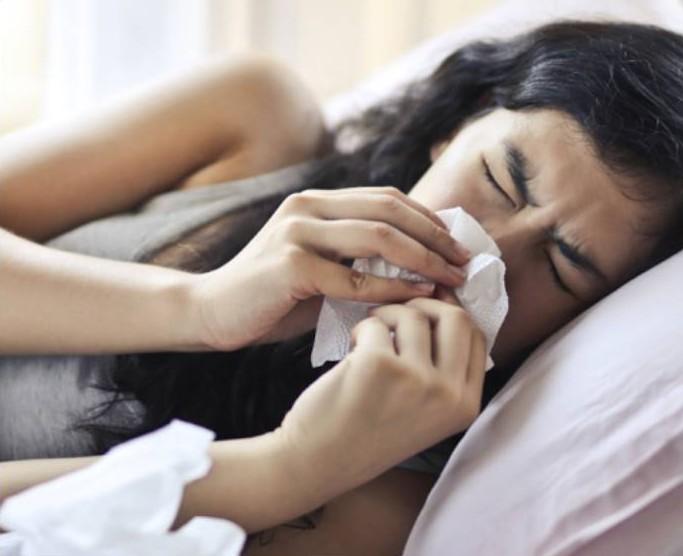 woman sick in bed quarantining.
